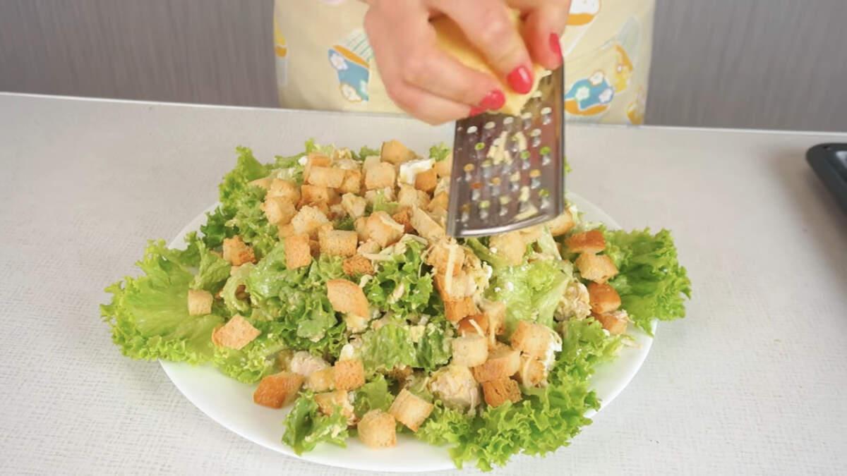 Салат перекладываем на блюдо.  Сверху посыпаем оставшимися сухариками и украшаем тертым сыром.