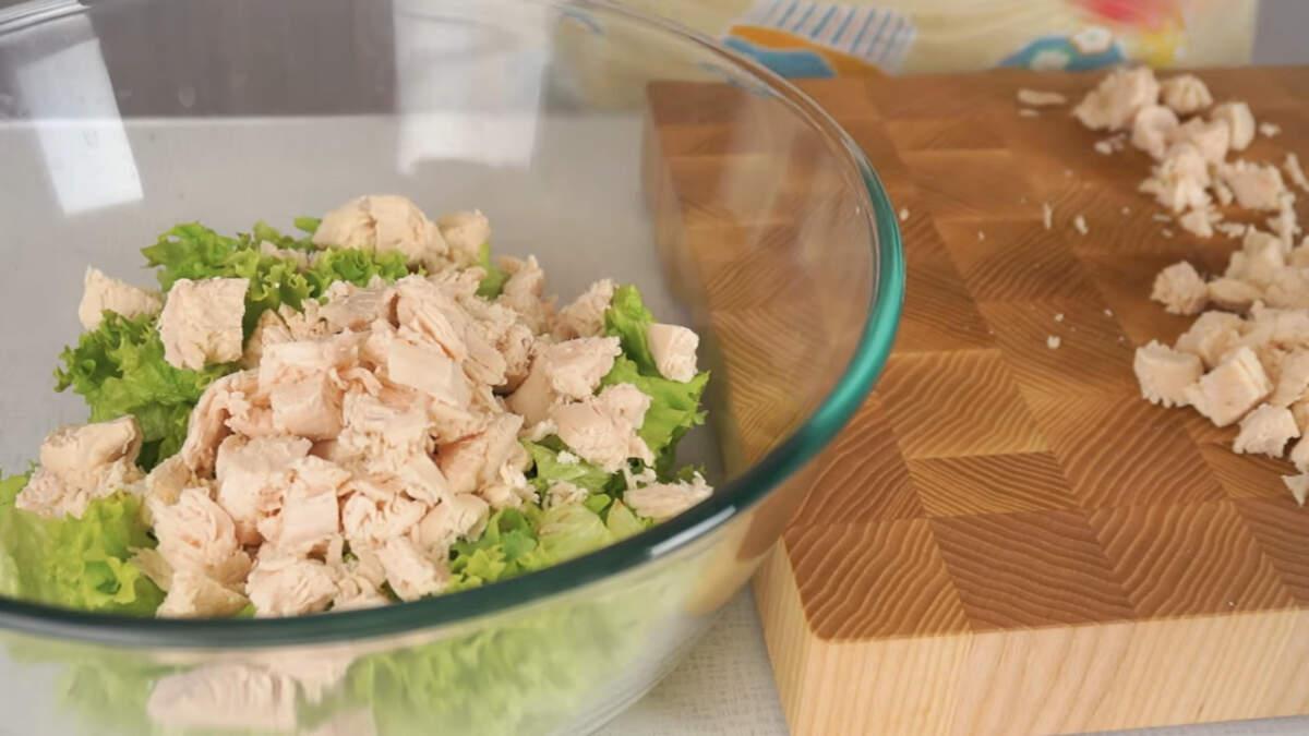 Нарезанные листья салата и куриное филе перекладываем в большую миску.