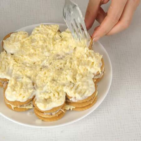 На крекер выкладываем половину сырной массы с чесноком.