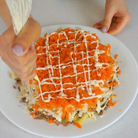 Следующим слоем выкладываем тертую морковь. Морковный слой немного солим.