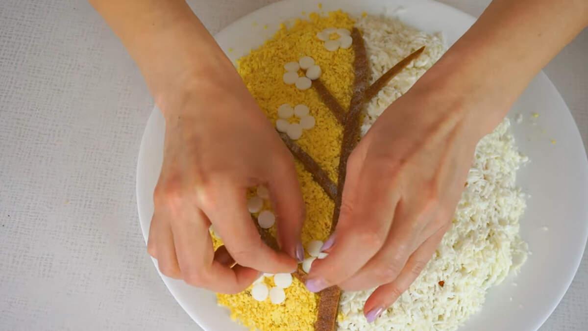 На желтую сторону салата выкладываем кружочки белка, формируя цветочки