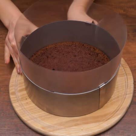 Складываем торт в раздвижном кулинарном кольце. По бокам кольца ставим ацетатную пленку и на дно кладем первый корж. Сжимаем кольцо до размера бисквита.