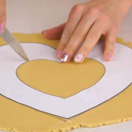 На раскатанный лист теста кладем бумажный шаблон и по нему ножом вырезаем сердце. Количество ингредиентов рассчитано на 2 торта, поэтому выпекаем 4 коржа.