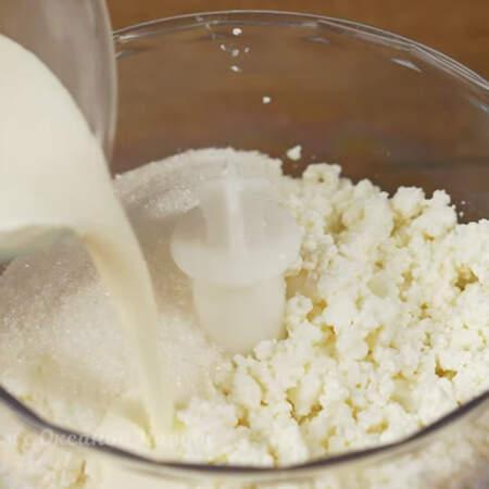 Теперь в измельчитель кладем 300 г творога жирностью 5 %. В этом рецепте можно использовать творог любой жирности. К творогу насыпаем 100 г сахара и наливаем примерно 70 мл сливок или сметаны.