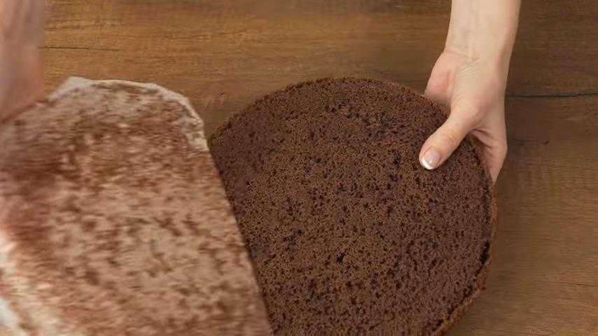 Разрезаем бисквит на 2 примерно одинаковых коржа. С верхнего коржа снимаем запеченную корочку.