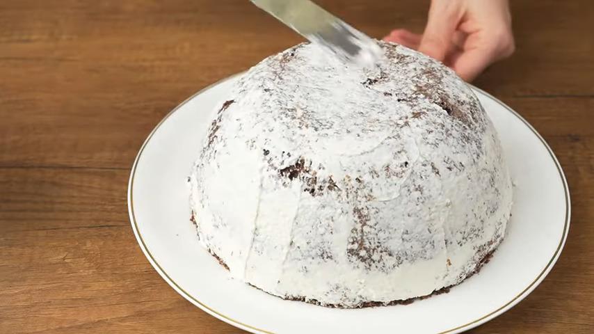 Приготовленными сливками обмазываем торт. Сначала наносим тонкий черновой слой, чтобы прибить крошки.  А затем наносим оставшийся крем.