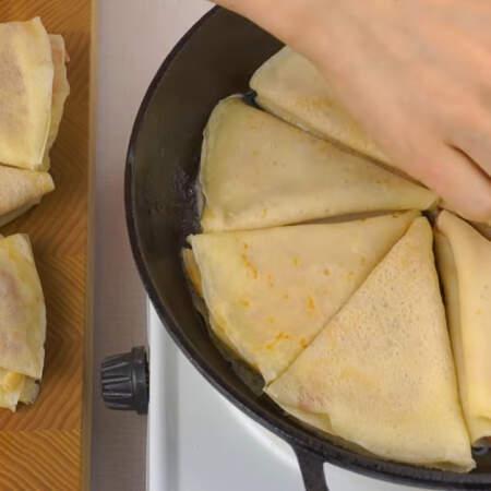 На разогретую сковороду наливаем немного подсолнечного масла и кладем кусочек сливочного масла для вкуса. Уже подготовленные начиненные блинчики выкладываем на сковороду.