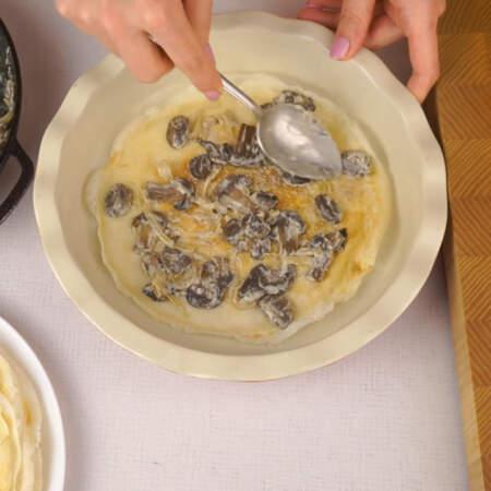Собираем закусочный торт. Дно формы для запекания смазываем сливочным маслом. Кладем блин, на него выкладываем грибную начинку