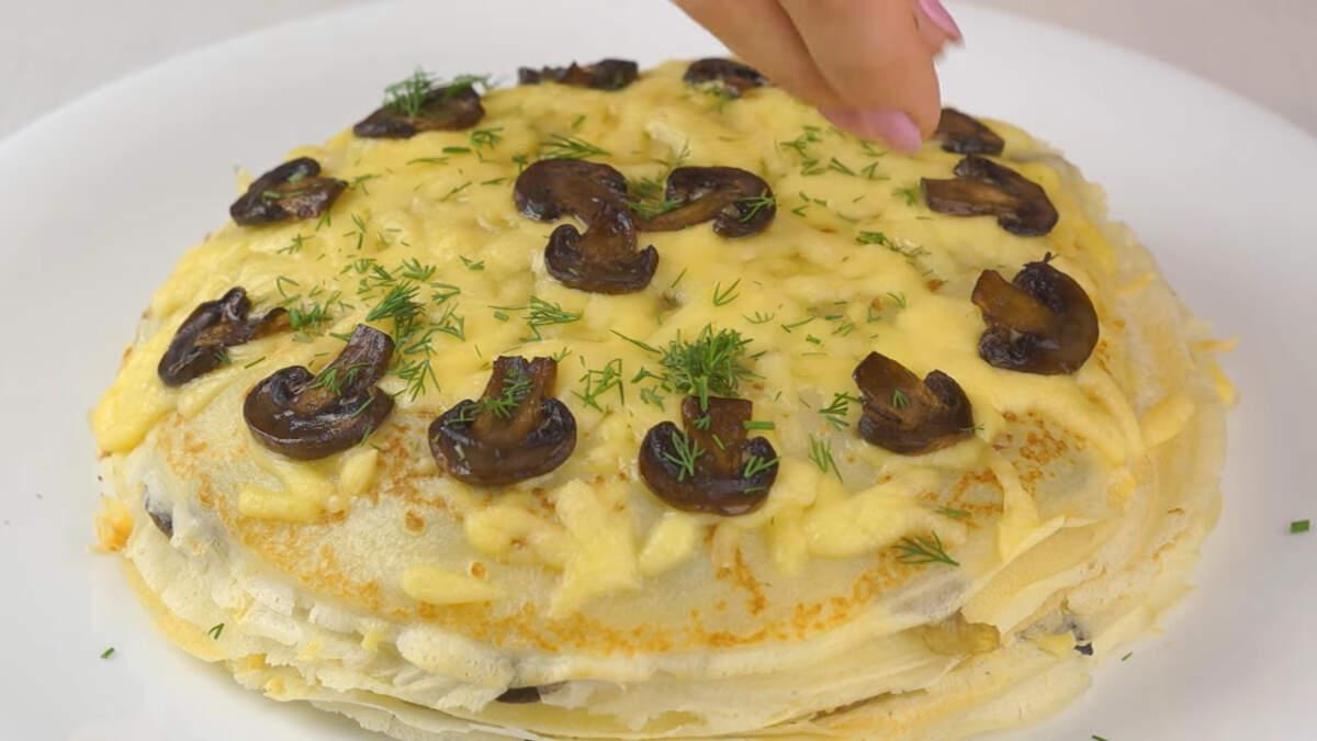 Запеченный блинный торт перекладываем на блюдо. Сверху закусочный торт украшаем порезанным укропом.