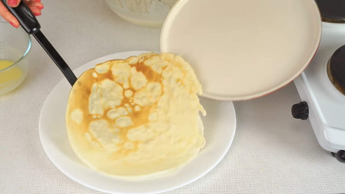 Сразу же блины перекладываем на тарелку. Хочу заметить, что при жарке всех последующих блинов сковороду не нужно смазывать маслом, т.к. масло есть уже в тесте и блины не будут прилипать к сковороде. Но если вдруг понадобится, то конечно можно смазать сковороду дополнительно.  Перед каждым блином тесто немного перемешиваем, чтобы равномерно распределить масло в тесте.