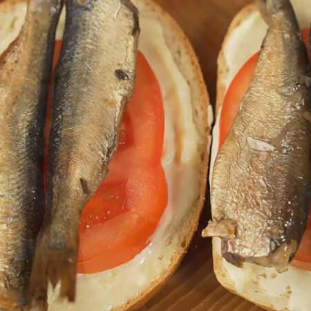 На помидоры кладем по 2 рыбки. Для 12 бутербродов понадобится две сто шестидесяти граммовые баночки шпротов.