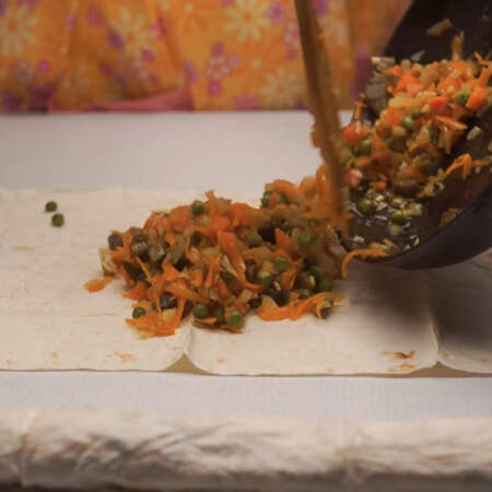 Делаем два длинных овощных рулета. Берем лист лаваша и на него выкладываем половину овощной начинки.
