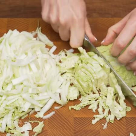 0,5 кг пекинской капусты мелко шинкуем ножом. Пекинскую капусту можно заменить молодой белокочанной капустой.