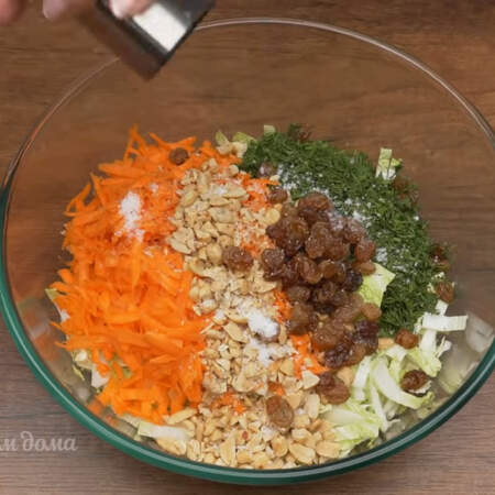 В миску кладем подготовленную капусту, морковь, укроп, насыпаем измельченный арахис и изюм. Все солим по вкусу и перчим.