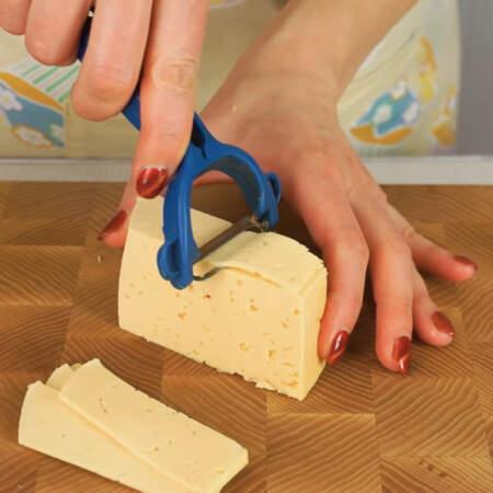 150 г сыра сыра сначала нарезаем овощечисткой на тонкие пластинки.