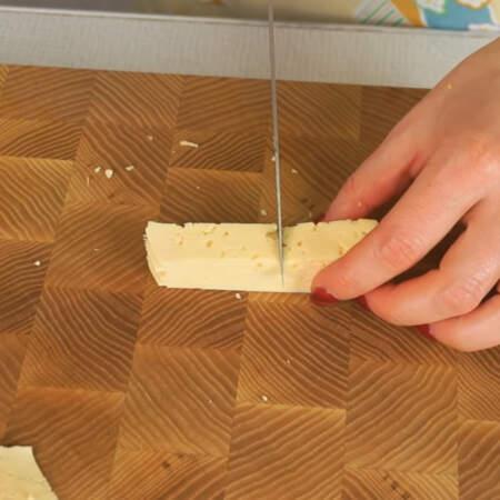 Пластинки нарезаем на примерно одинаковые прямоугольники. Также нарезаем тонкие, длинные полоски сыра.