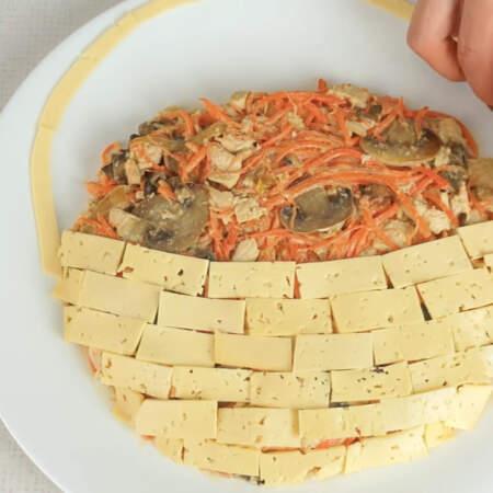 Нарезанный сыр выкладываем на одной половине салата в шахматном порядке. Имитируем плетеную корзинку. Из тонких полосок сыра формируем ручку для корзинки.