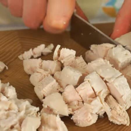 300 г отваренной куриной грудки нарезаем кубиками.