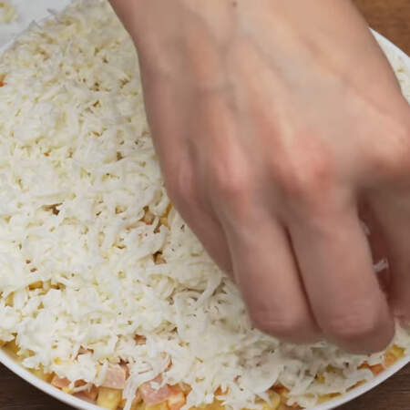 Сверху на салат выкладываем равномерным слоем тертые белки.