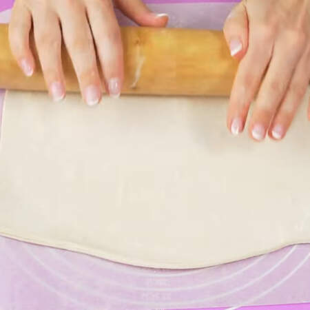 Сначала испечем коржи. Для торта понадобится 900 г готового слоеного бездрожжевого теста.  Лист теста кладем на пергаментную бумагу немного присыпанную мукой. Лист теста раскатываем в ширину примерно в полтора раза.