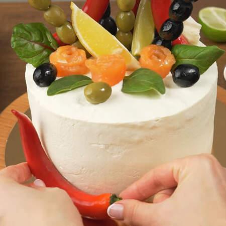 По низу торта кладем стручок красного перца и оливки.