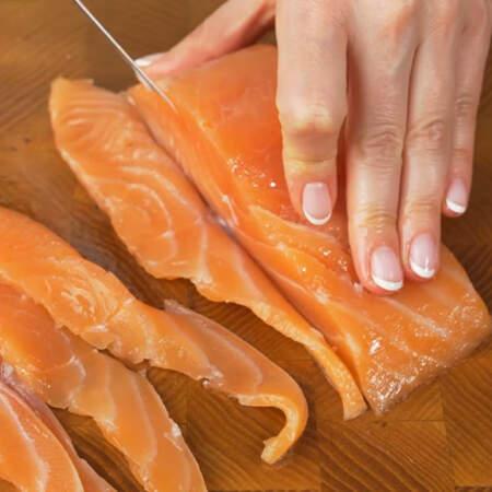 Теперь приготовим начинку для торта. Берем 250 г красной соленой рыбы и отрезаем от нее несколько длинных не толстых пластинок.