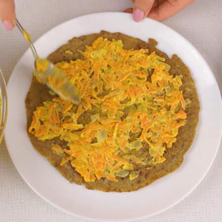 На блюдо кладем первый печеночный блин и смазываем его сверху морковной начинкой. Накрываем вторым блином.