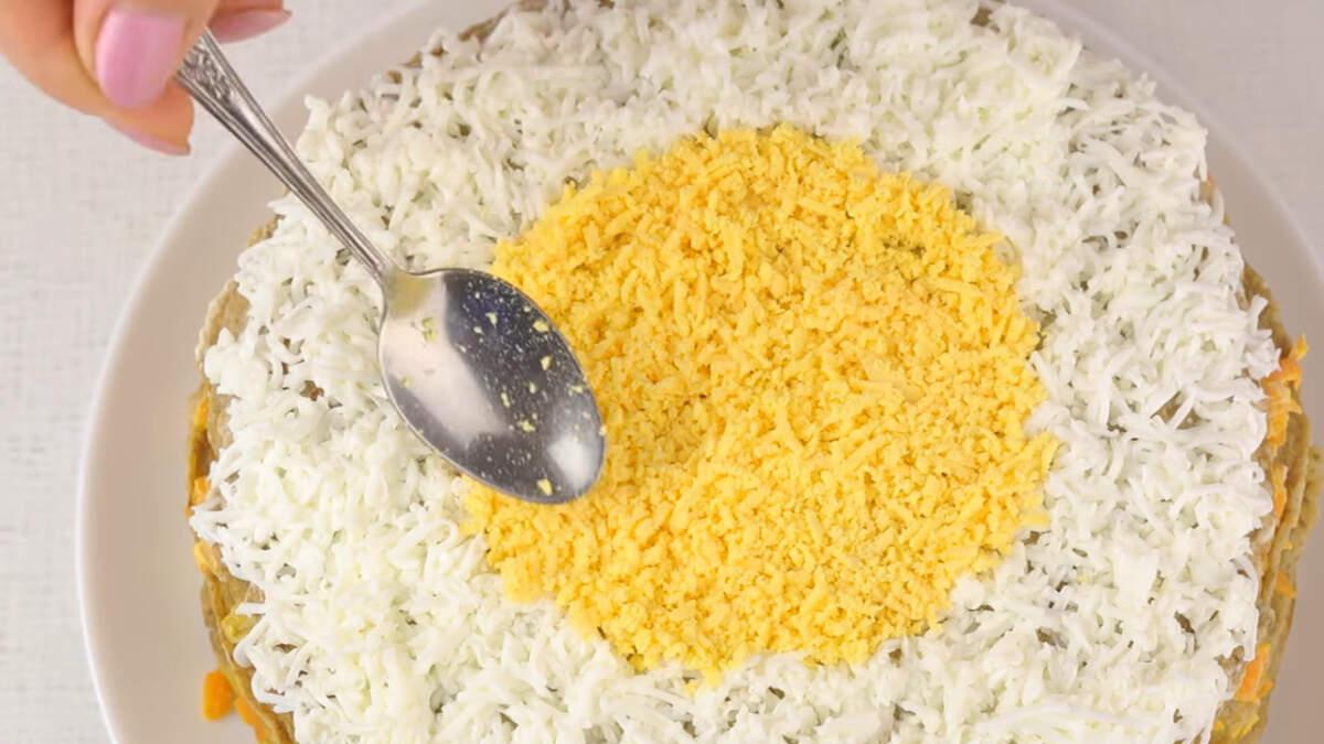 Сверху по краю торт посыпаем тертым белком, а в середине желтком. Украшаем торт веточкой петрушки