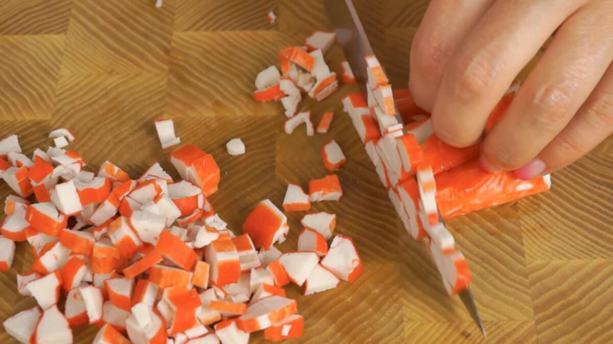 Сначала подготовим крабовые палочки.  Их нужно нарезать полукольцами.