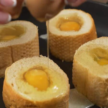 В каждую серединку багета аккуратно разбиваем по одному яйцу.