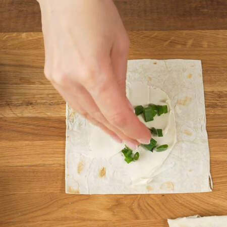 Кладем кусочек лаваша. По центру смазываем плавленным сыром. Я использую плавленый сыр Янтарь. Мне для 200 г лаваша понадобилось 120 г сыра. Сверху сыр посыпаем нарезанным зеленым луком.