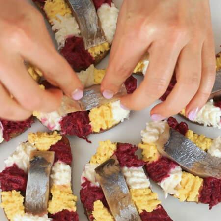 Каждый из кусочков сельди выкладываем в центр бутерброда.