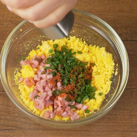 К подготовленным желткам добавляем нарезанную колбасу и зеленый лук. Сюда же насыпаем 0,5 ч.л. молотой красной сладкой паприки. Перчим черным молотым перцем.