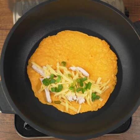 С одной стороны лепешки кладем начинку. Выкладываем подготовленное мясо, тертый сыр и зеленый лук.