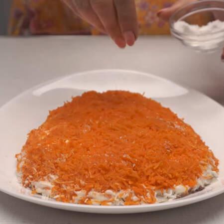Следующим слоем выкладываем тертую морковь.Сверху морковь немного солим