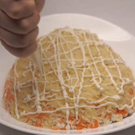 На морковный слой кладем тертый картофель. И опять наносим сеточку из майонеза.