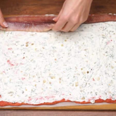 На бисквит, смазанный сливочной начинкой кладем с одного края подготовленное филе сельди.