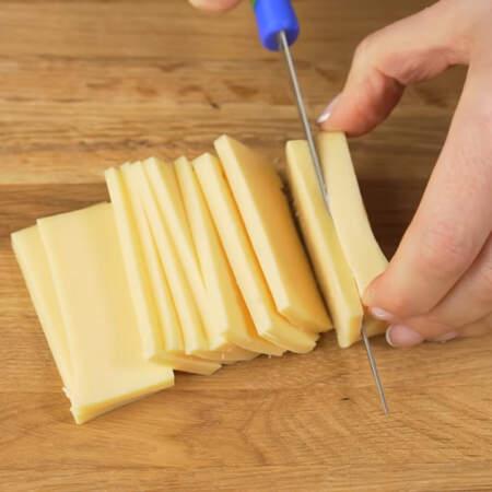 Сначала подготовим все ингредиенты. 80 г сыра нарезаем сначала пластинками. А затем пластинки режем брусочками.