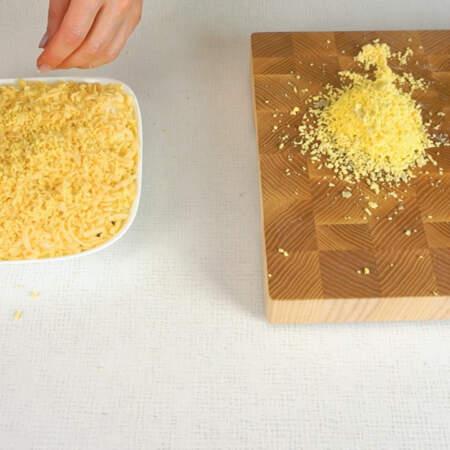 Тертые желтки кладем сверху на салат на слой из сыра.