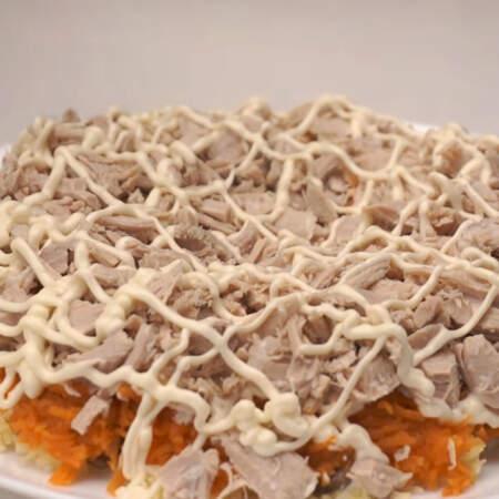 Четвертым слоем кладем порезанное мясо. Делаем сеточку из майонеза.
