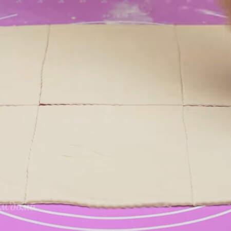 Раскатанный лист теста разрезаем на 6 примерно одинаковых квадратов. Всего понадобится 2 листа готового слоеного бездрожжевого теста общей массой 450 г.