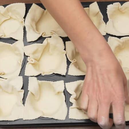 В подготовленные формочки выкладываем нарезанные кусочки теста формируя из них корзинки.