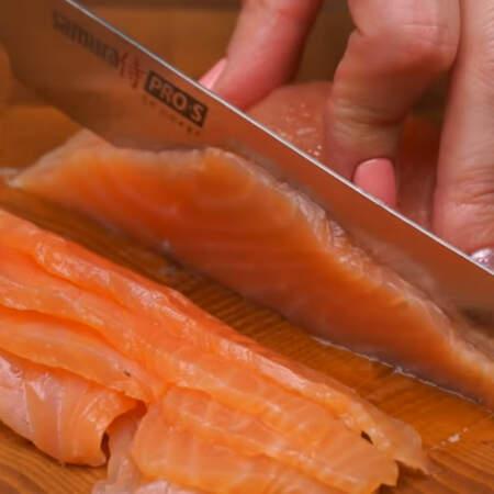 Берем примерно 100 г красной соленой рыбы и нарезаем ее пластинками.