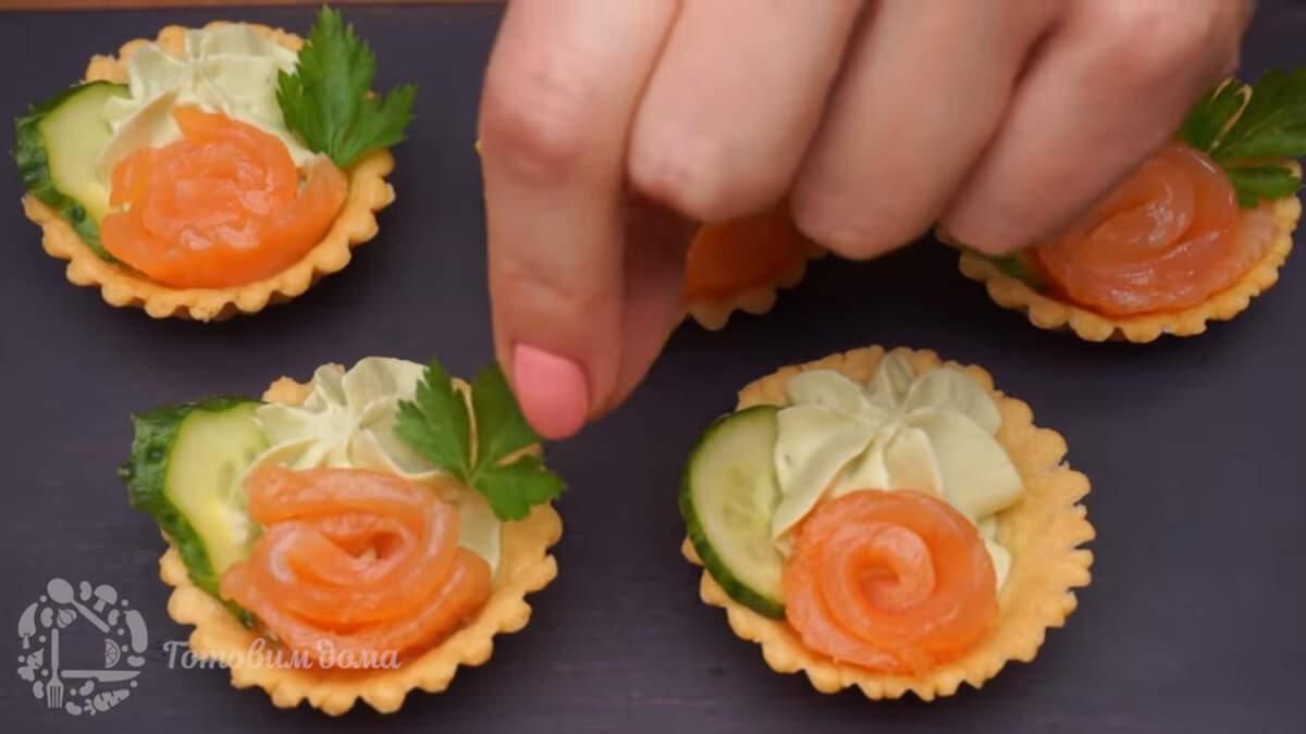В каждую тарталетку сбоку вставляем по одному кусочку огурца и листик петрушки. Корзиночки готовы, можно подавать на стол.