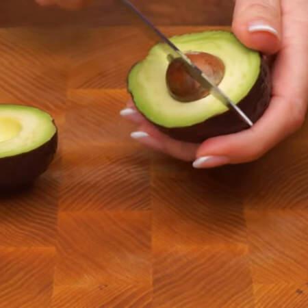 Подготовим начинку. 1 спелое авокадо разрезаем пополам и вынимаем косточку.