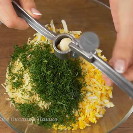В миску кладем тертый сыр, подготовленные яйца и насыпаем укроп. Немного солим. Сюда же выдавливаем 2-3 зубчика чеснока через пресс.