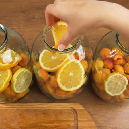 Сверху в каждую банку кладем по одному кружочку лимона. Дальше кладем по 3 кружочка апельсина.