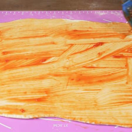 Раскатанное тесто смазываем томатным соусом или кетчупом.
