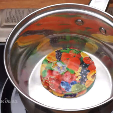 Стерилизуем крышки. Крышки с резинками кладем в сотейник, заливаем водой и ставим на плиту.