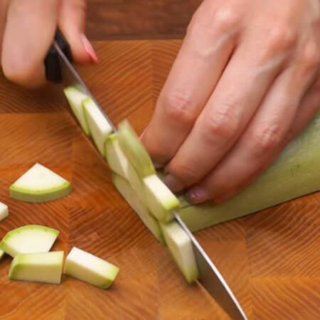 1 молодой кабачок разрезаем вдоль на две части. Затем каждую часть разрезаем еще раз пополам и нарезаем четверть кружочками. Если у кабачка толстая кожура, то ее лучше срезать.